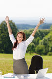 Businesswoman in sunny nature office hands up Stock Photo