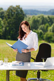 Businesswoman in sunny nature office look folder Stock Photography