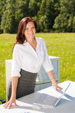 Businesswoman in sunny nature office smile. Young businesswoman in sunny nature office smiling standing behind table royalty free stock photography