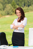 Businesswoman in sunny nature smiling crossed arms Royalty Free Stock Photography
