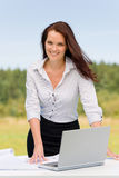 Businesswoman in sunny nature smiling with laptop Stock Photos