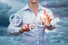 Businesswoman supports the gear mechanism. Stock Photography