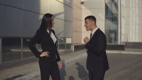 Businesswoman swears with man employee. Successful woman director of large firm swears with man employee standing on the background of city office building on stock footage