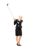 Businesswoman swinging a golf club Royalty Free Stock Images