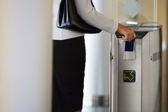 Businesswoman swiping card in entrance barrier, rear view, mid-section (differential focus) Stock Photo