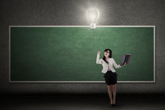 Businesswoman switch on a bright light bulb Stock Photos