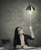 Businesswoman switching on idea light bulb Stock Photography