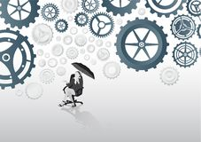Businesswoman in swivel chair holding umbrella under cogs and wheels Stock Photos
