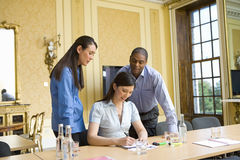 Businesswoman at table writing in notepad flanked by colleagues Royalty Free Stock Photos