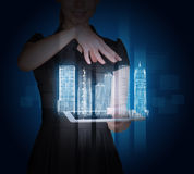 Businesswoman with tablet and 3d city model. On abstract blue background Royalty Free Stock Photo