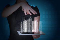 Businesswoman with tablet and 3d model of city. Businesswoman with tablet and 3d city model on abstract blue background Royalty Free Stock Photo