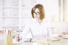 Businesswoman with tablet doing paperwork Royalty Free Stock Images