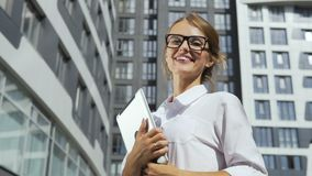 Businesswoman with tablet in front of corporation. Smiling and self-confident young dark hair caucasian businesswoman, in a white blouse and stylish glasses, is stock footage