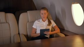 Businesswoman with tablet pc inside of business jet stock video