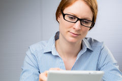 Businesswoman with a Tablet. A businesswoman uses a tablet computer at work Royalty Free Stock Photos