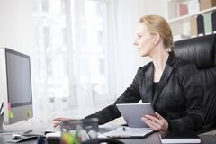 Businesswoman with Tablet Using a Desktop Computer Royalty Free Stock Image