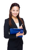 Businesswoman take note on clipboard Stock Image