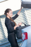 Businesswoman takes bag out from the car Stock Images