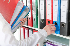 Businesswoman taking binders from a shelf Royalty Free Stock Image