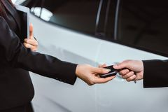 Businesswoman taking a car key from a salesman. Close up businesswoman is taking a car key from a car salesman stock photography