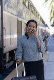 Businesswoman taking on cell phone at train station Royalty Free Stock Photo