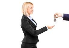 Businesswoman taking keys from a businessman Stock Photo