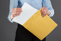 Businesswoman taking letter out of envelope Stock Photography