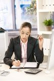 Businesswoman taking notes. Into organizer, sitting at desk in bright office holding glasses Stock Photo