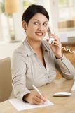 Businesswoman taking notes. Happy businesswoman working at desk in office, writing notes while talking on phone Royalty Free Stock Image