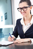 Businesswoman taking notes. Smiling businesswoman taking notes in office Royalty Free Stock Image