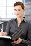 Businesswoman taking notes. To personal organizer in office Royalty Free Stock Photography