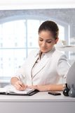 Businesswoman taking notes. Smiling smart businesswoman taking notes into personal organizer in office Royalty Free Stock Photography