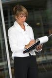 Businesswoman taking notes. Pretty blond businesswoman taking notes Stock Images