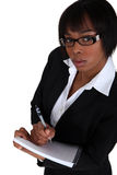 Businesswoman taking notes. An African American businesswoman taking notes Stock Image