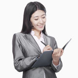 Businesswoman taking notes in her notebook Stock Photo