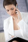Businesswoman taking notes and making phone call. Businesswoman taking notes into personal organizer, concentrating on mobile phone call Royalty Free Stock Photos