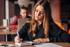 Businesswoman taking notes in Notepad sitting in cafe royalty free stock photo
