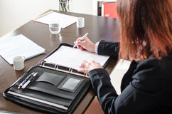Businesswoman taking notes. At office Stock Photography
