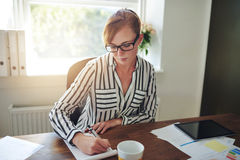Businesswoman taking notes on a phone call Stock Photos