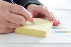 Businesswoman taking notes. On a post-it Royalty Free Stock Photography