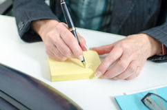 Businesswoman taking notes on a post it Stock Photo