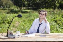 Businesswoman taking notes while talking. Business woman taking notes while talking Stock Image