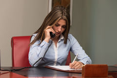 Businesswoman Taking Notes And Talking On Phone. Beautiful Young Woman Working Taking Notes And Talking On Phone- Businesswoman Working Online Stock Photography