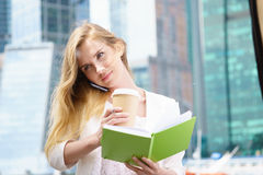 Businesswoman taking notes. White talking by phone and drinking coffee Stock Images