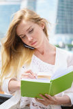 Businesswoman taking notes. White talking by phone and drinking coffee Stock Photography