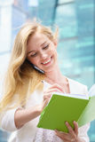 Businesswoman taking notes. White talking by phone and drinking coffee Royalty Free Stock Photo