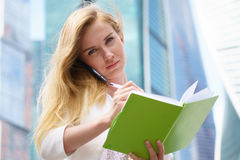 Businesswoman taking notes. White talking by phone and drinking coffee Royalty Free Stock Images