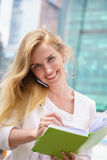 Businesswoman taking notes. White talking by phone and drinking coffee Royalty Free Stock Image