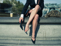 Businesswoman taking off her shoe in the city royalty free stock photo
