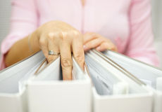 Businesswoman is taking one binder from the others Stock Photography